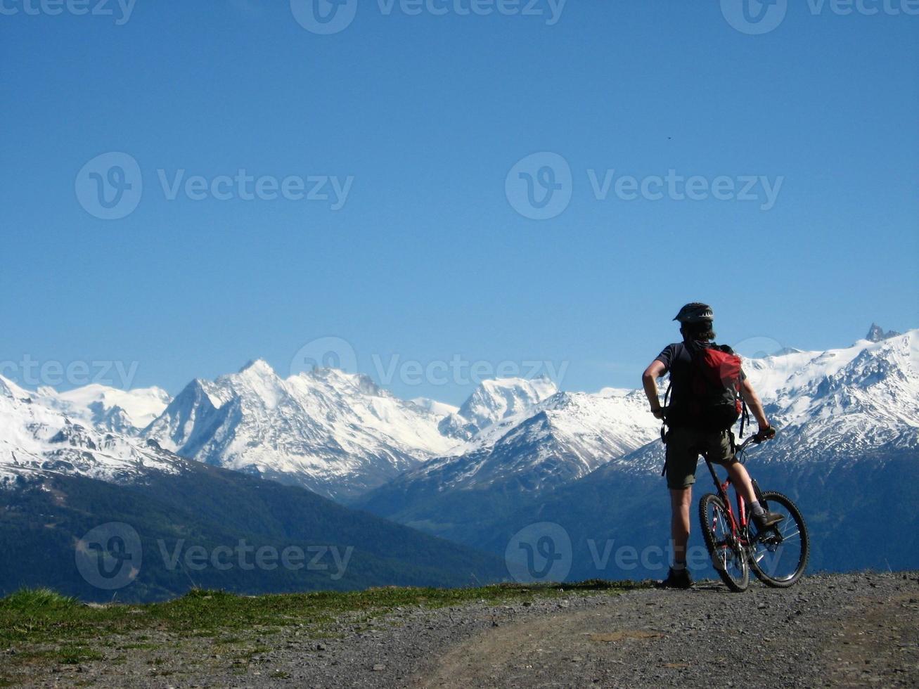 motociclista da montanha, desfrutando de uma vista dos Alpes foto