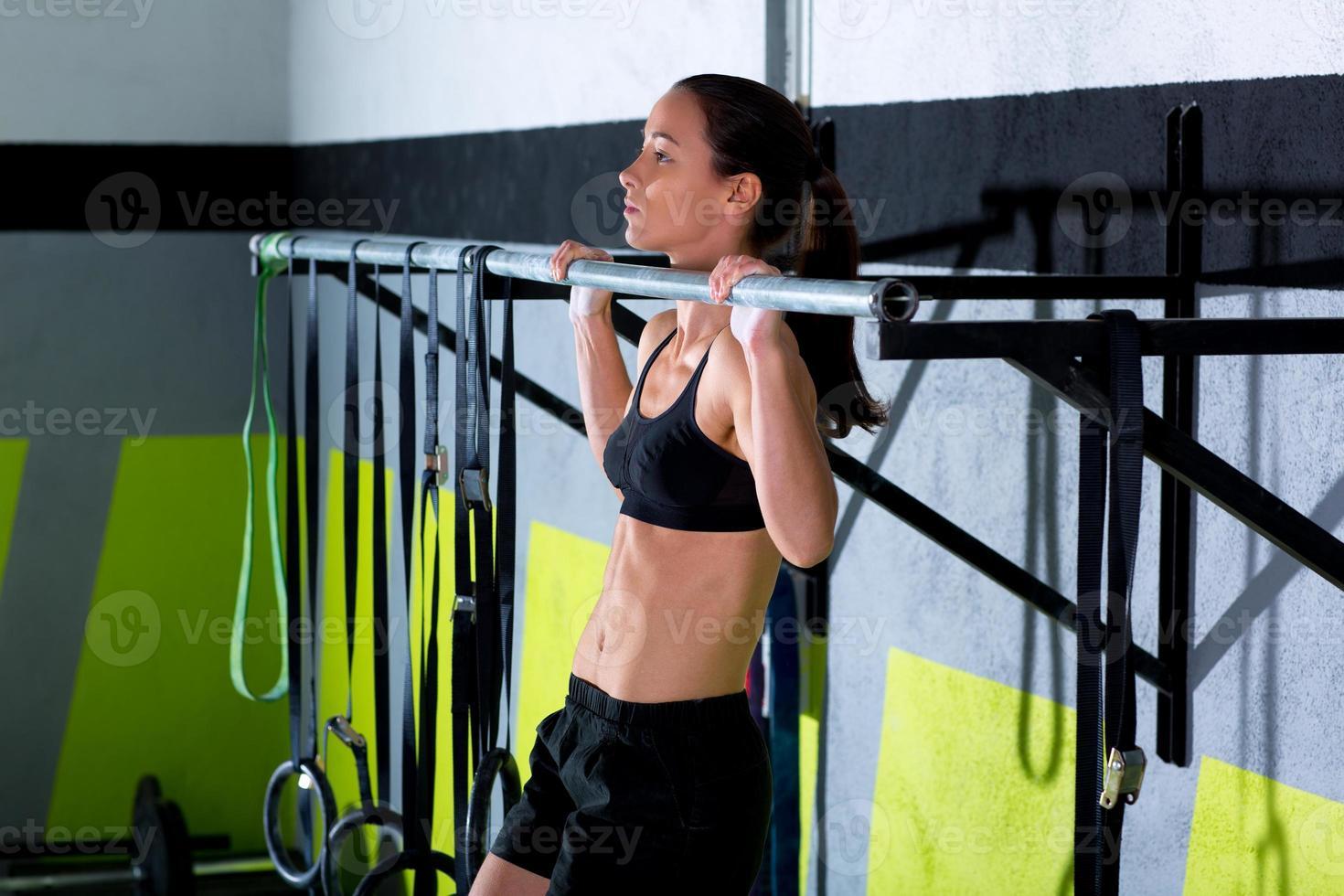 dedos do pé do ginásio para bar mulher pull-ups treino de 2 barras foto