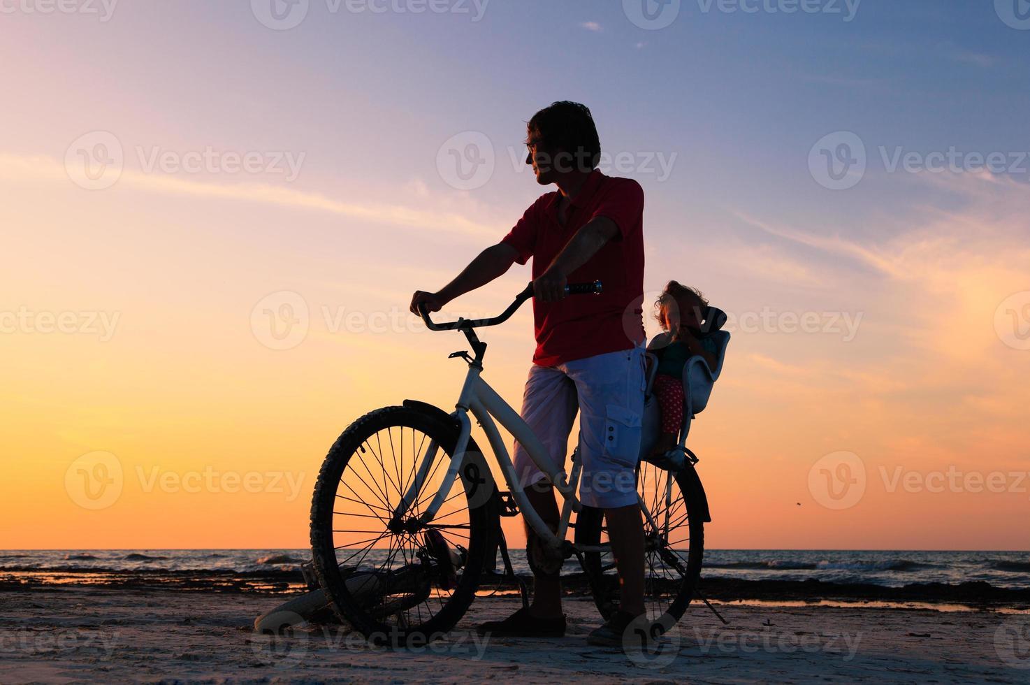 silhueta de pai e bebê, andar de bicicleta ao pôr do sol foto