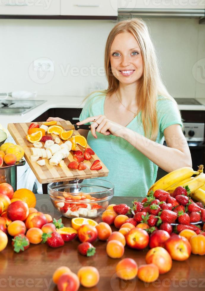 mulher loira feliz cortar frutas foto