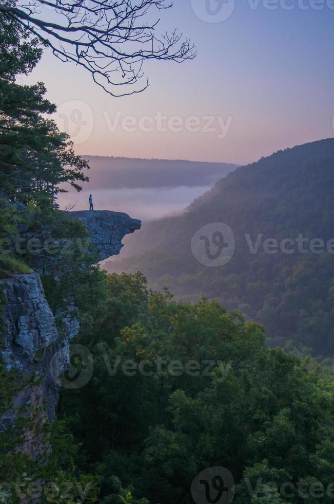 alpinista de pé em um penhasco rochoso alto foto