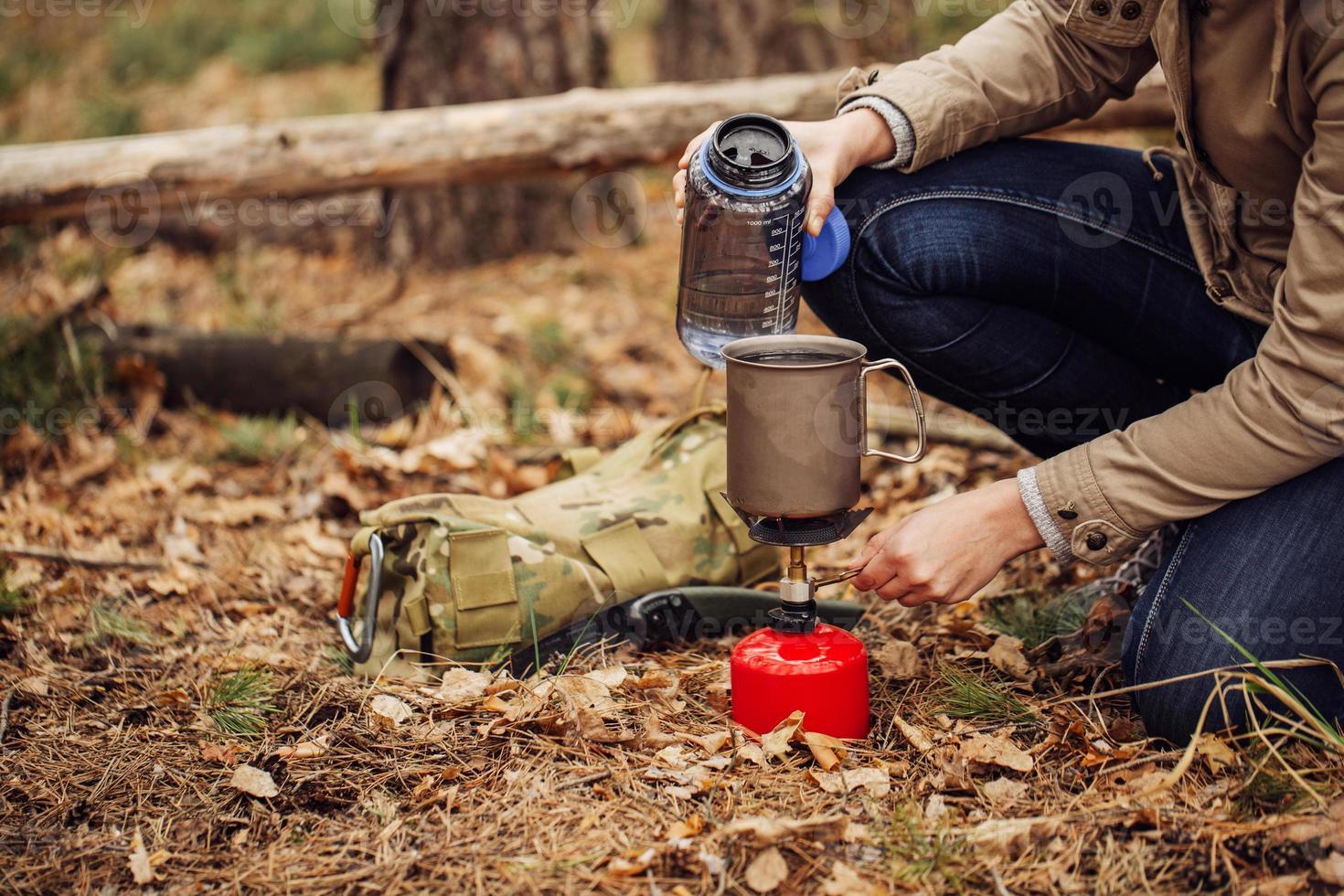 mulher derrama água de uma garrafa em uma caneca foto