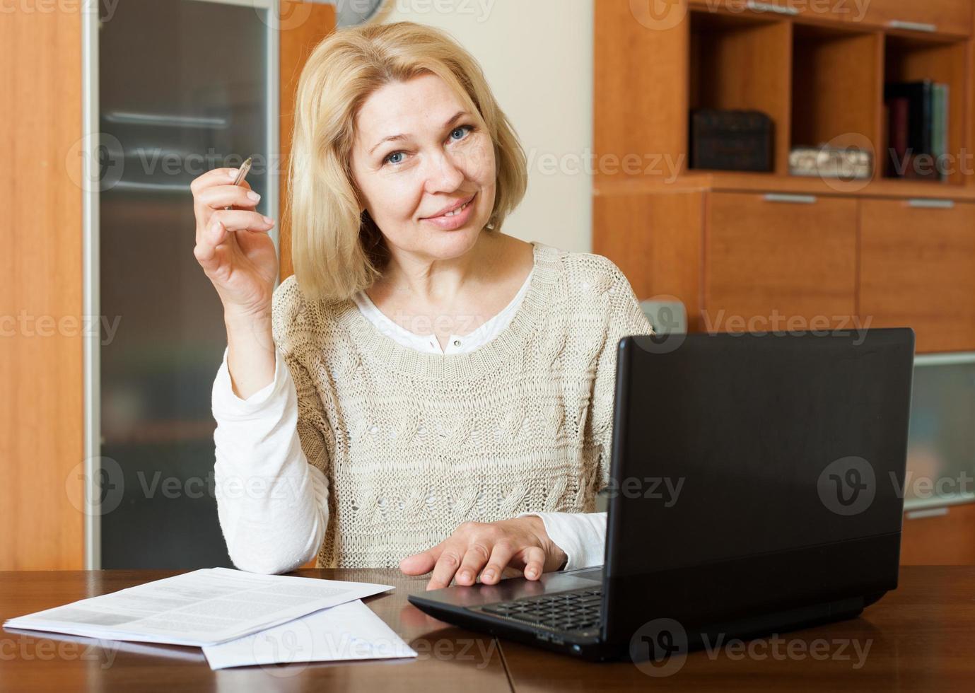 mulher madura com laptop e documentos financeiros foto