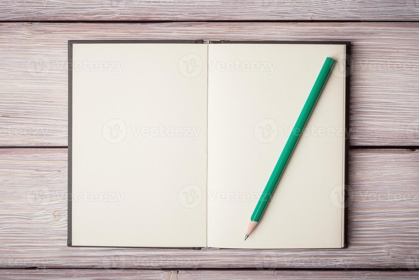 caderno aberto e um pancil na velha mesa de madeira foto