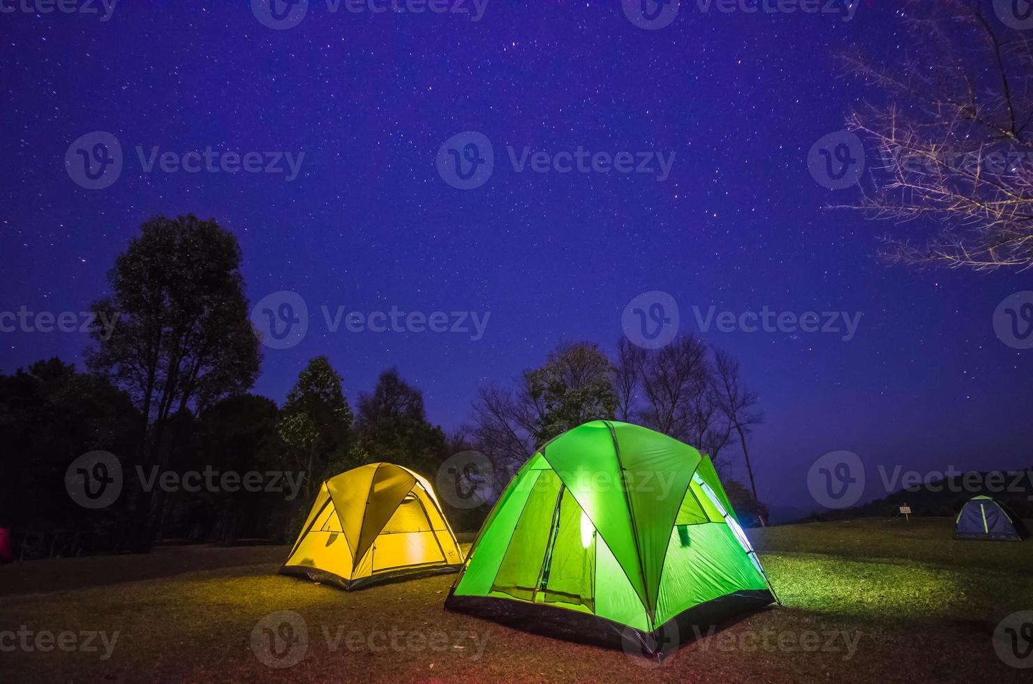 acampamento na floresta à noite com estrela foto