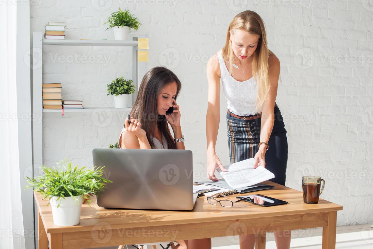 empresária falando e mostrando algo ao colega no escritório foto