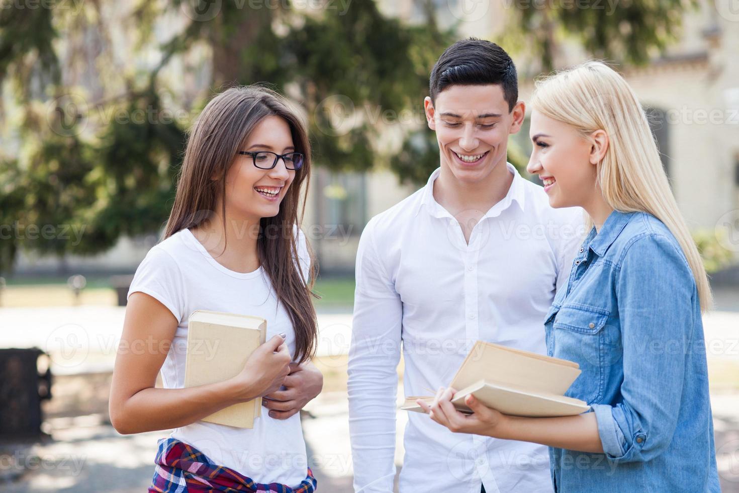 meninas e rapaz alegre estão estudando juntos foto