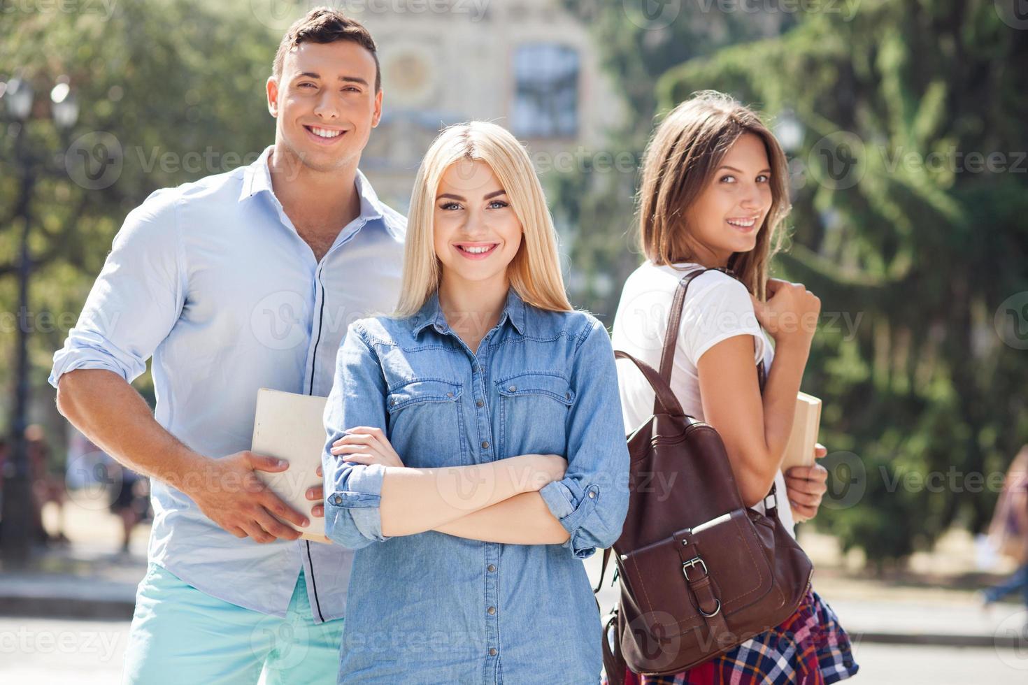 jovens amigos atraentes estão indo para a universidade foto