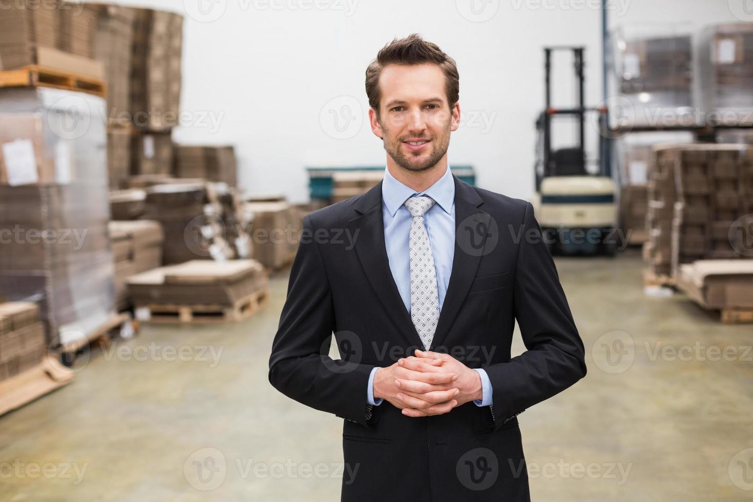 gerente de armazém em pé as mãos juntas foto
