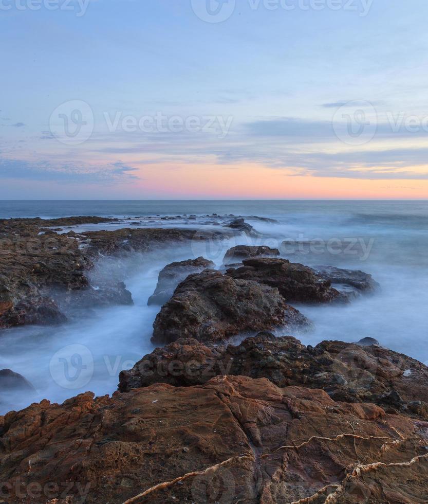 pôr do sol sobre as rochas em laguna beach foto