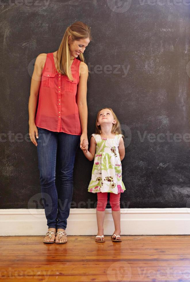 mãe e filha juntos de pé em casa foto