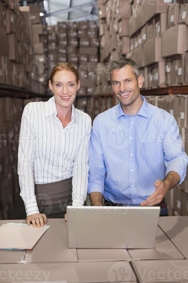 equipe de armazém trabalhando juntos no laptop foto