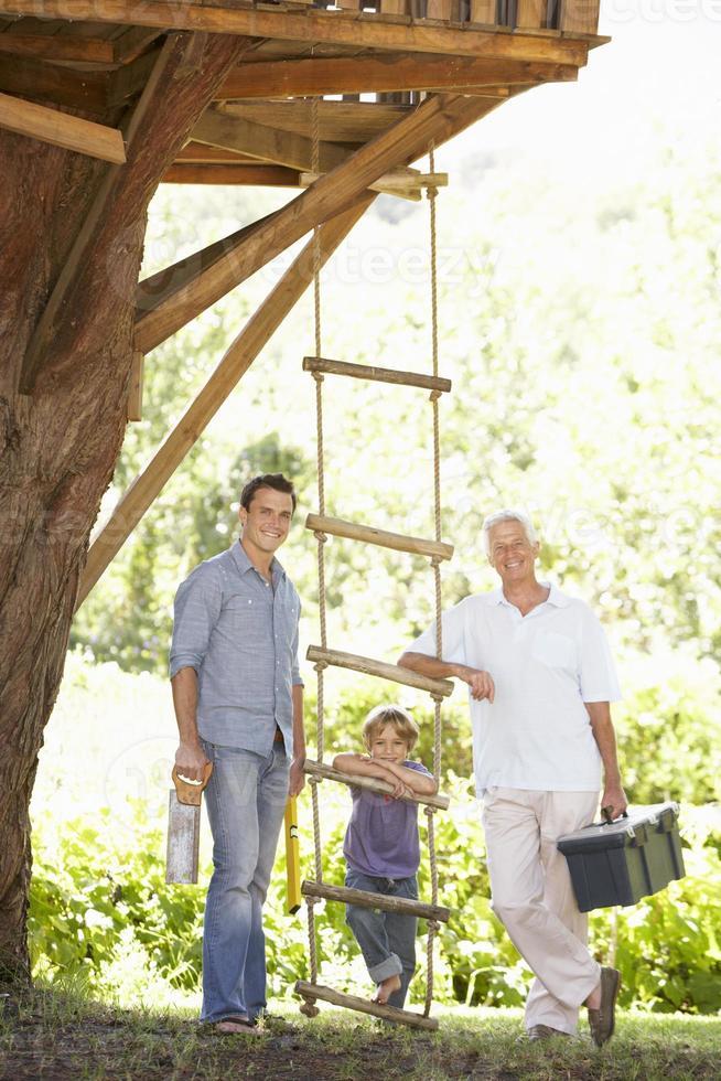 avô, pai e filho juntos a construção de casa na árvore foto