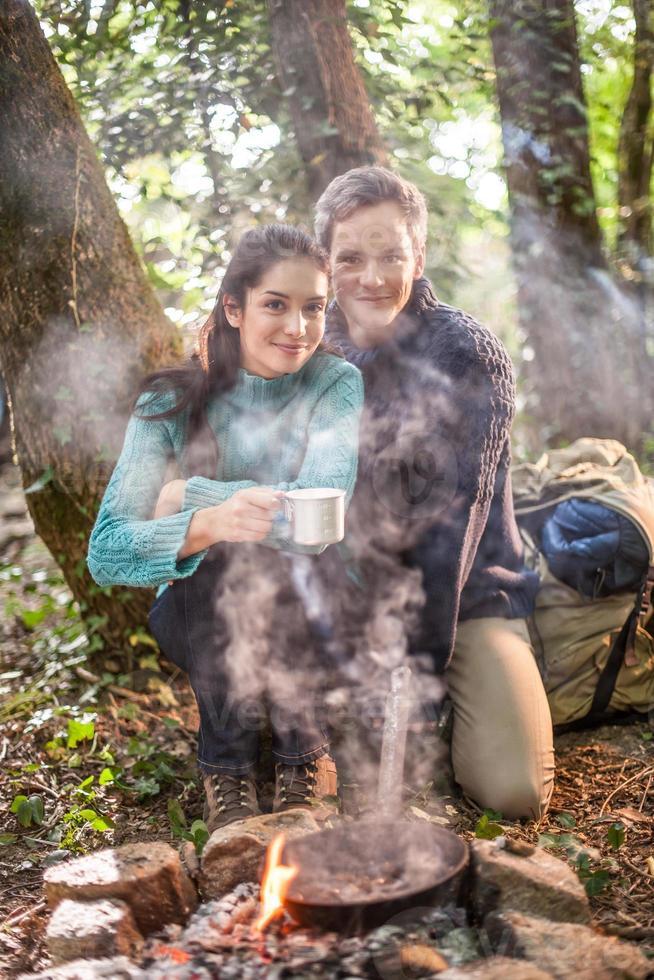 casal cozinhando em uma fogueira na floresta foto