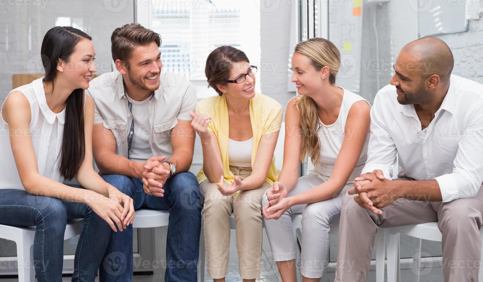 pessoas de negócios, conversando e trabalhando juntos em cadeiras foto