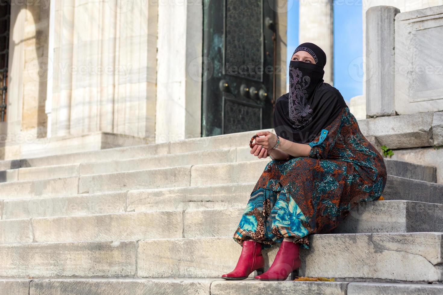 estilo muçulmano senhora vestida sentado degraus de mármore da mesquita azul foto