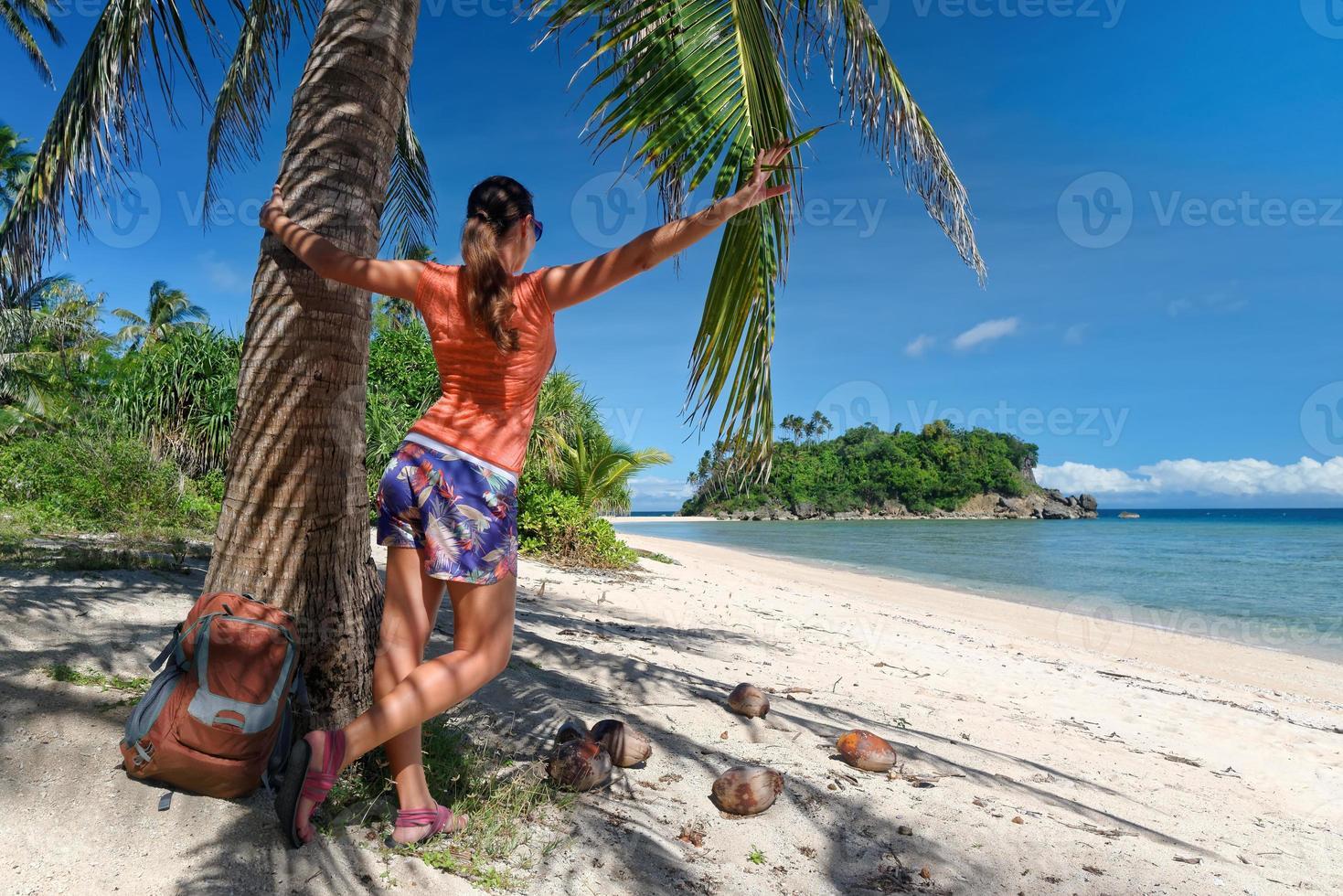 garota turista apreciando a vista da bela ilha e praia. foto
