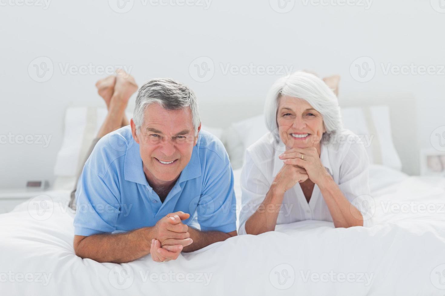 casal deitado juntos na cama foto