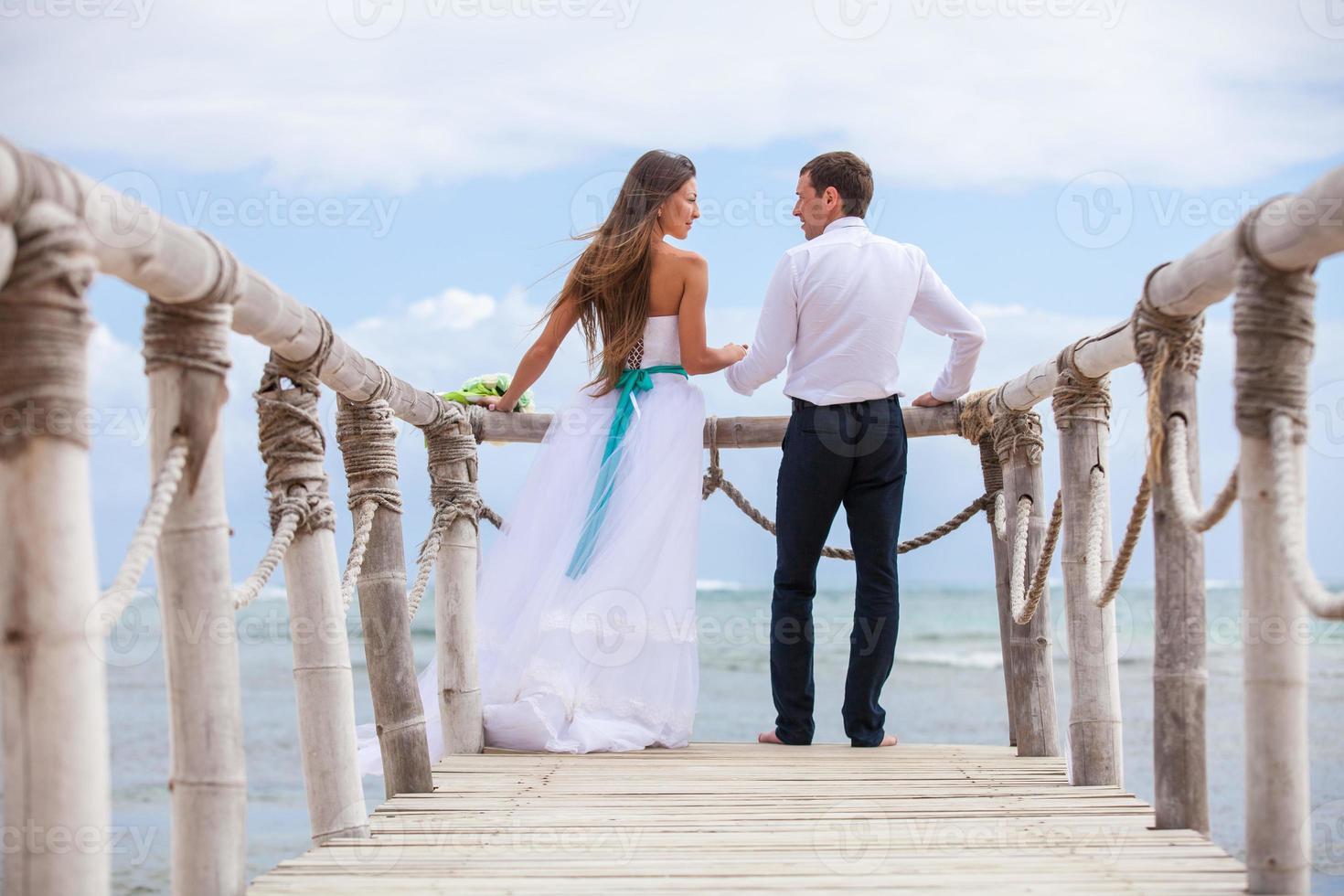 noiva e noivo juntos em um cais foto