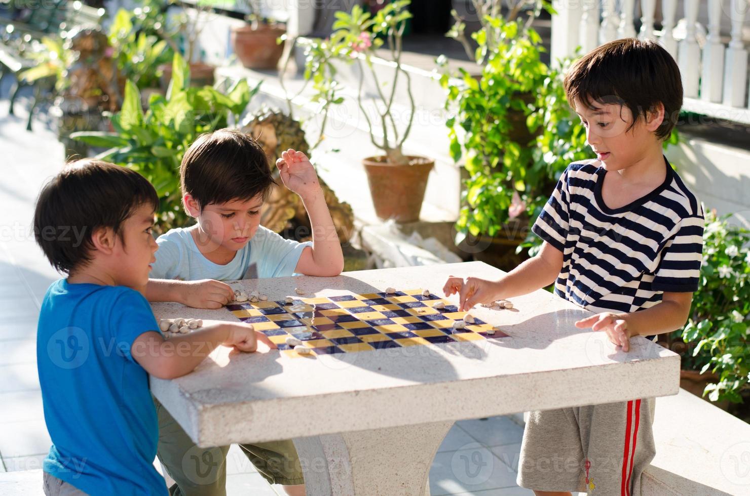 garoto jogando xadrez de pedra juntos foto