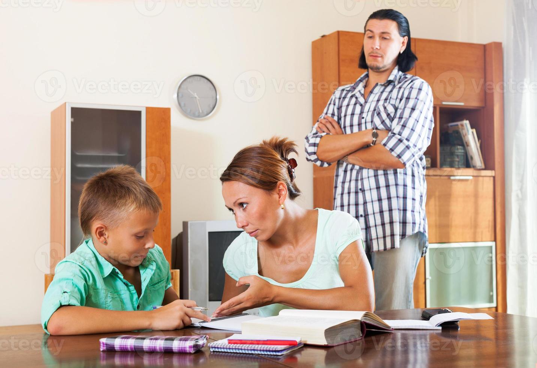 família comum fazendo lição de casa foto