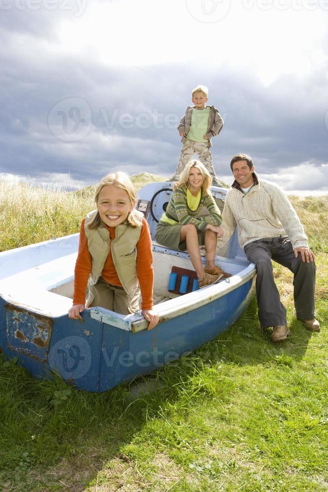 família jovem sentado no barco foto