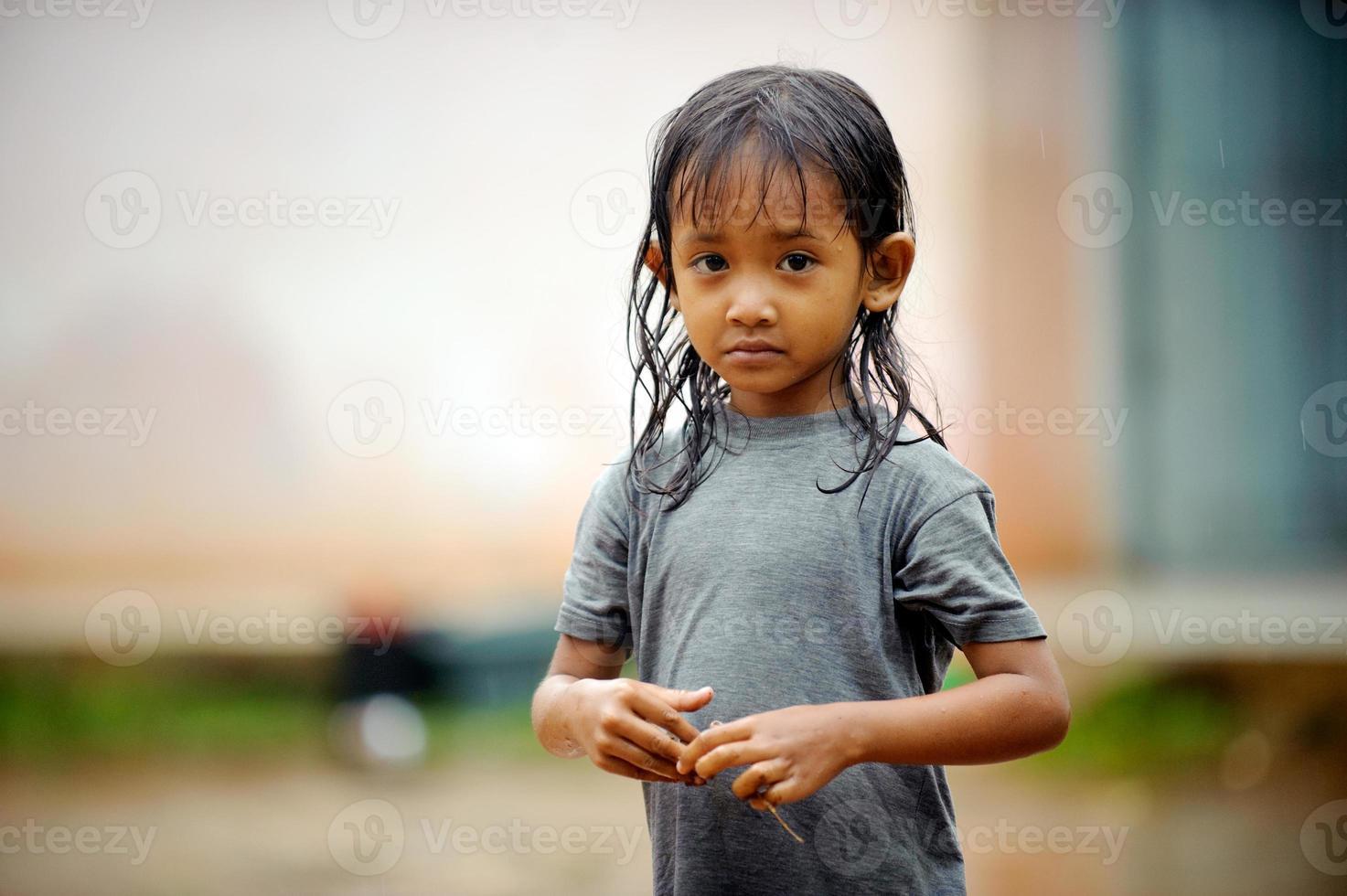 criança pobreza sob a chuva foto