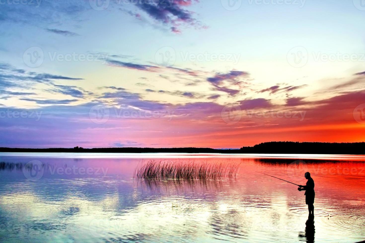 pescador com vara na beira do lago ao pôr do sol foto