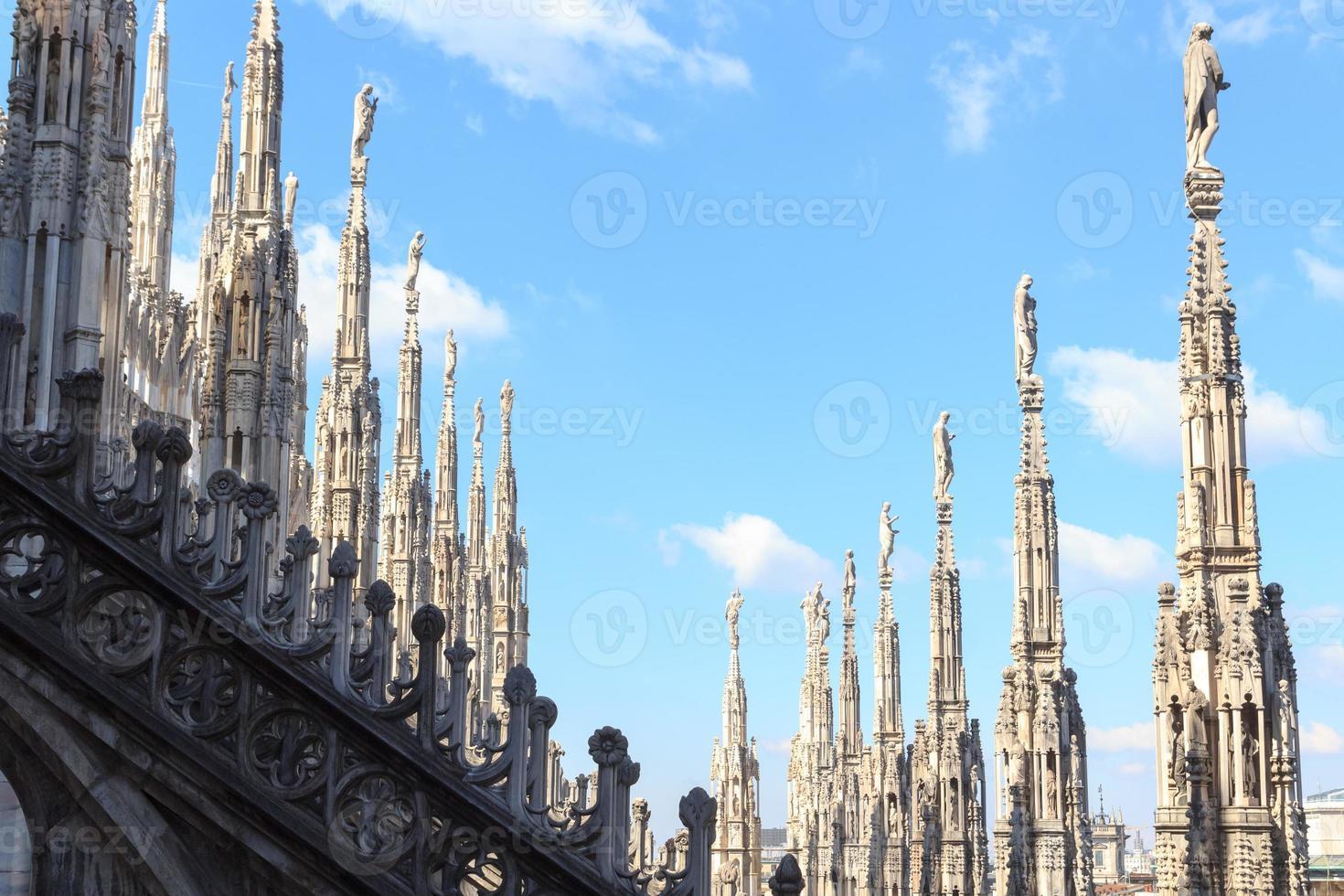 estátuas na catedral de Milão e céu azul foto