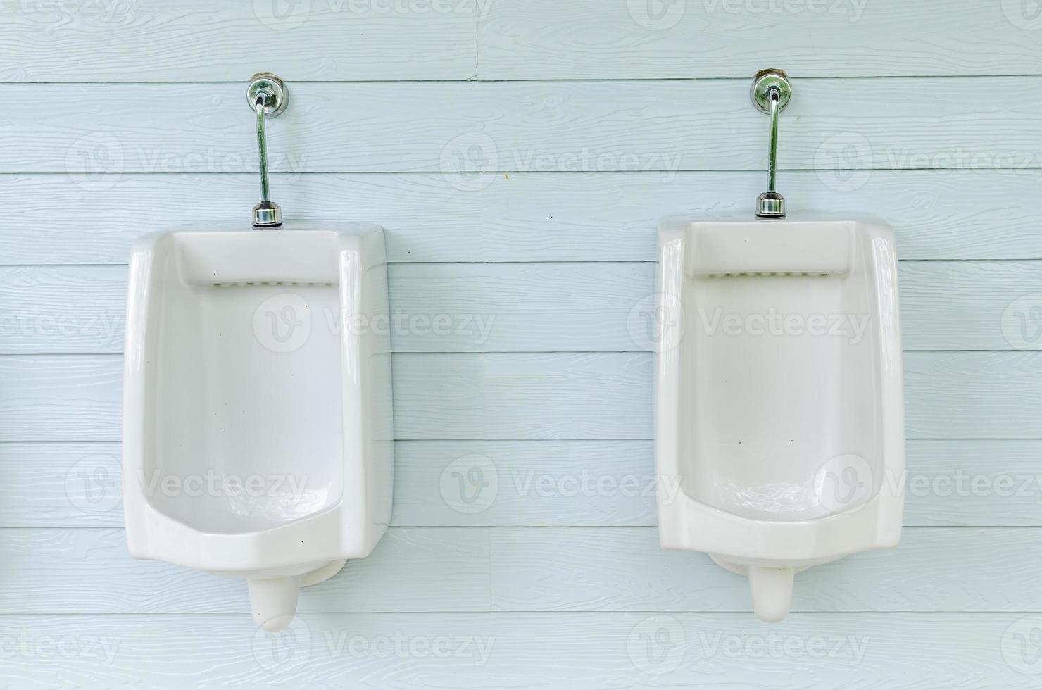 linha de mictórios brancos no banheiro masculino foto