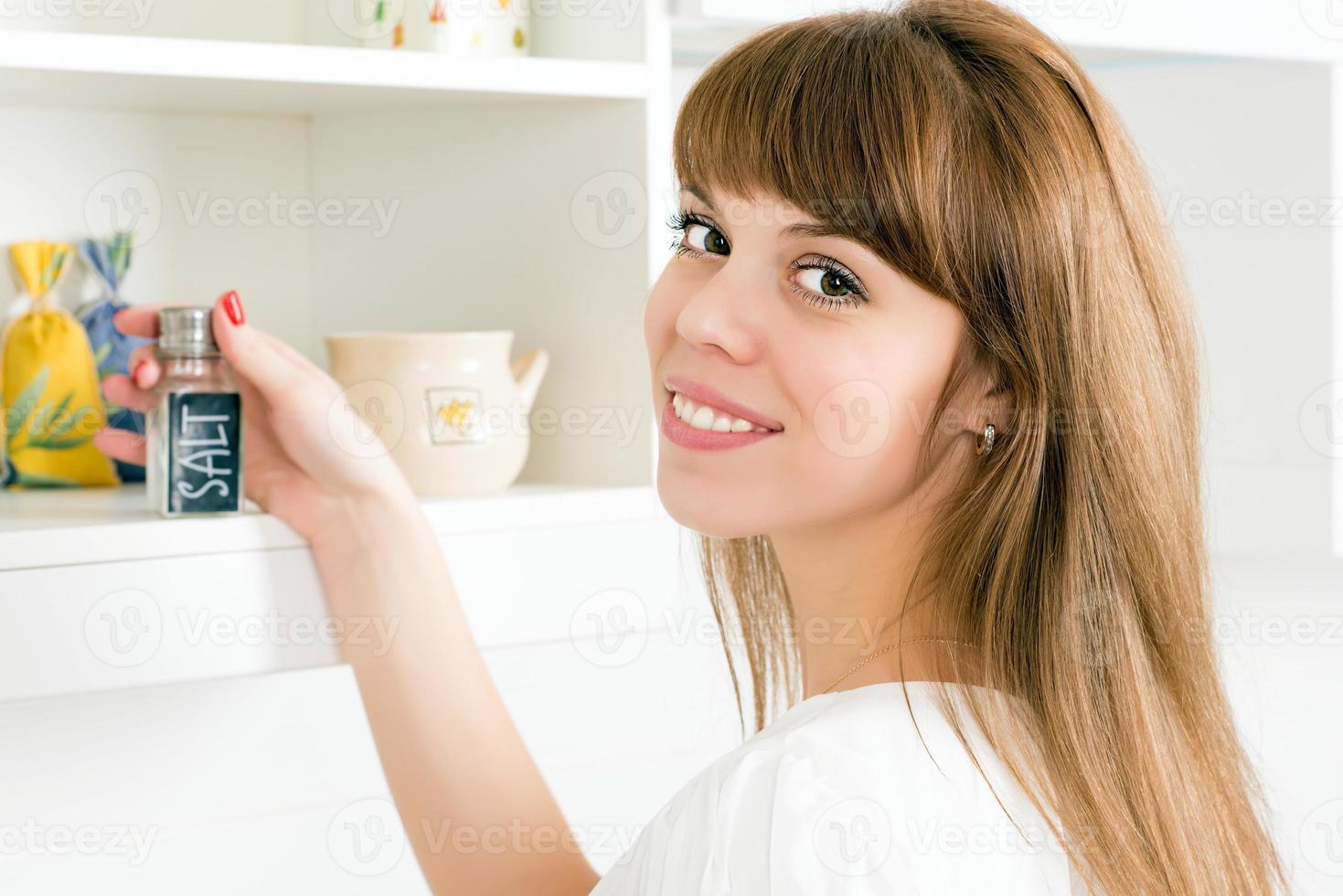 jovem fêmea tomando um saleiro foto