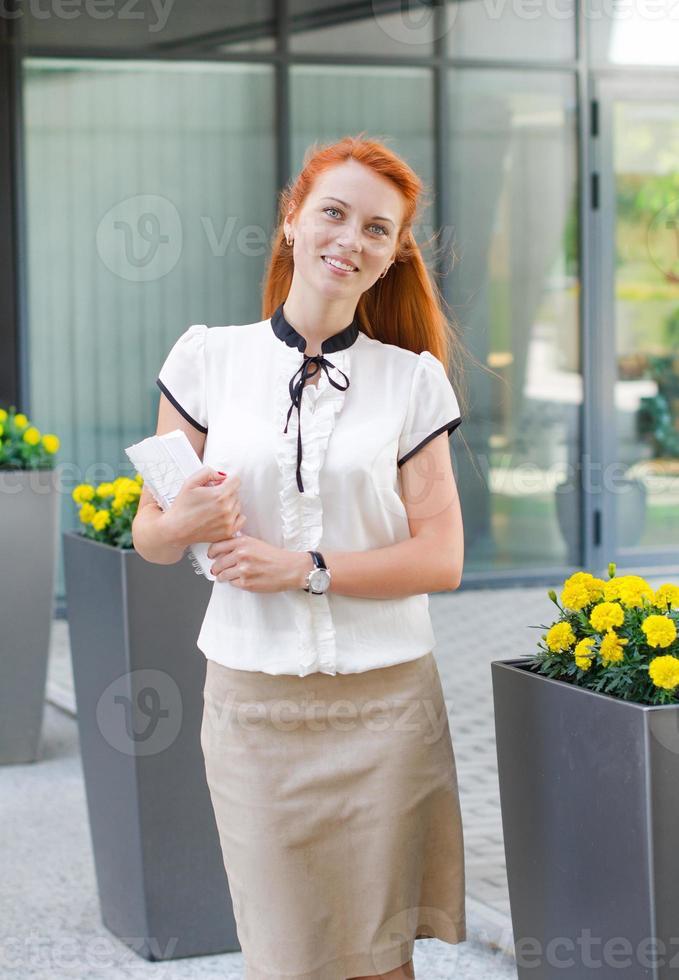 aluna caminhando ao ar livre com livro foto