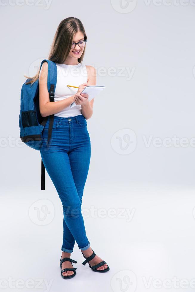 sorrindo feminino adolescente escrevendo notas no caderno foto