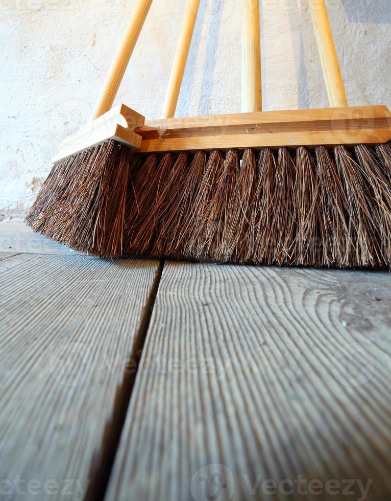 grandes vassouras no trabalho doméstico de piso de madeira foto