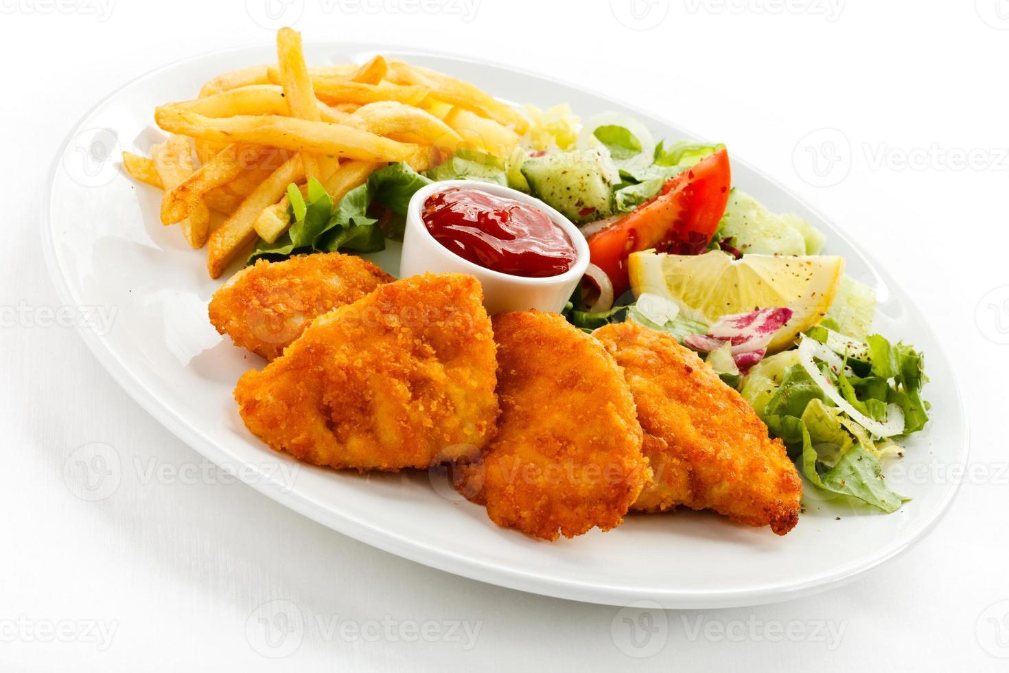 nuggets de frango frito, batata frita e legumes foto