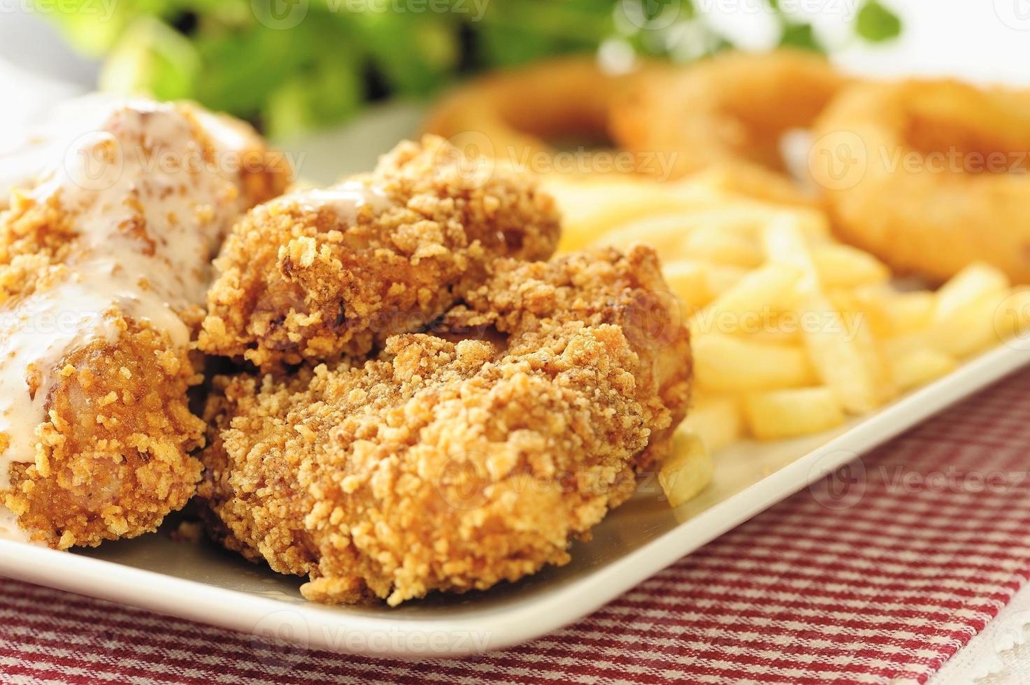 asas de frango com batatas fritas e rodelas de cebola foto