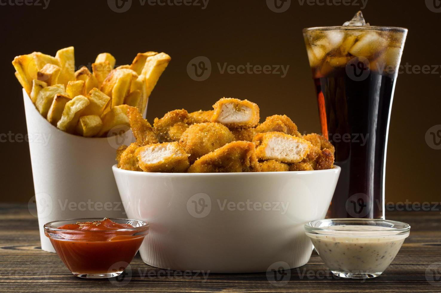 batatas fritas nuggets de frango e cola foto