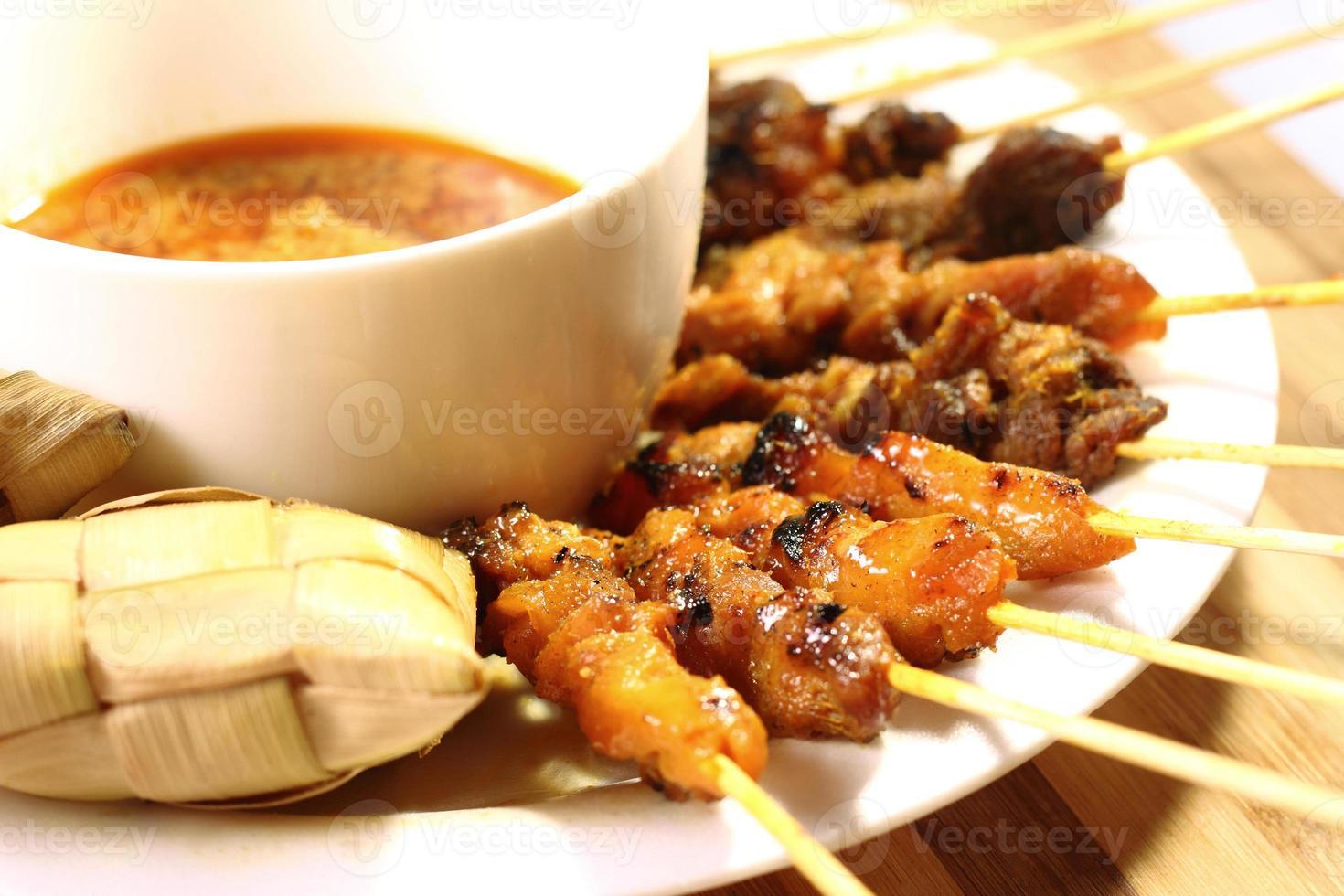 prato de comida satay em uma mesa de madeira foto