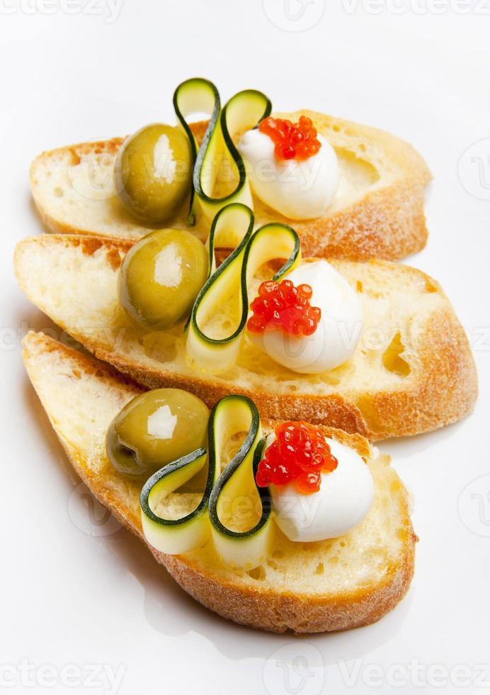 bruschetta com mussarela, azeitonas verdes, abobrinha e caviar vermelho foto