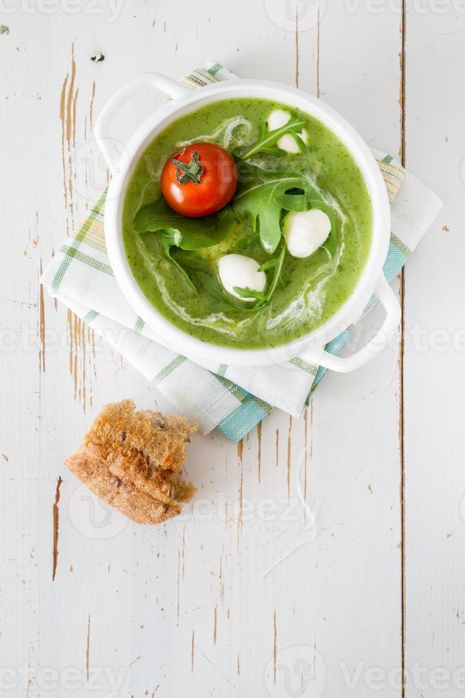 sopa pura verde com ruccola e tomate em tigela branca foto