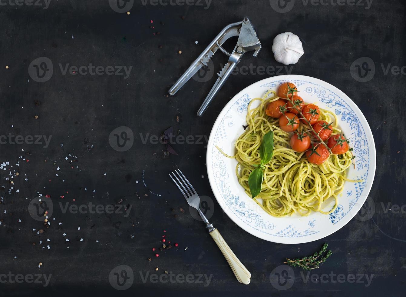 macarrão espaguete com molho pesto, manjericão, alho, tomate cereja assado foto