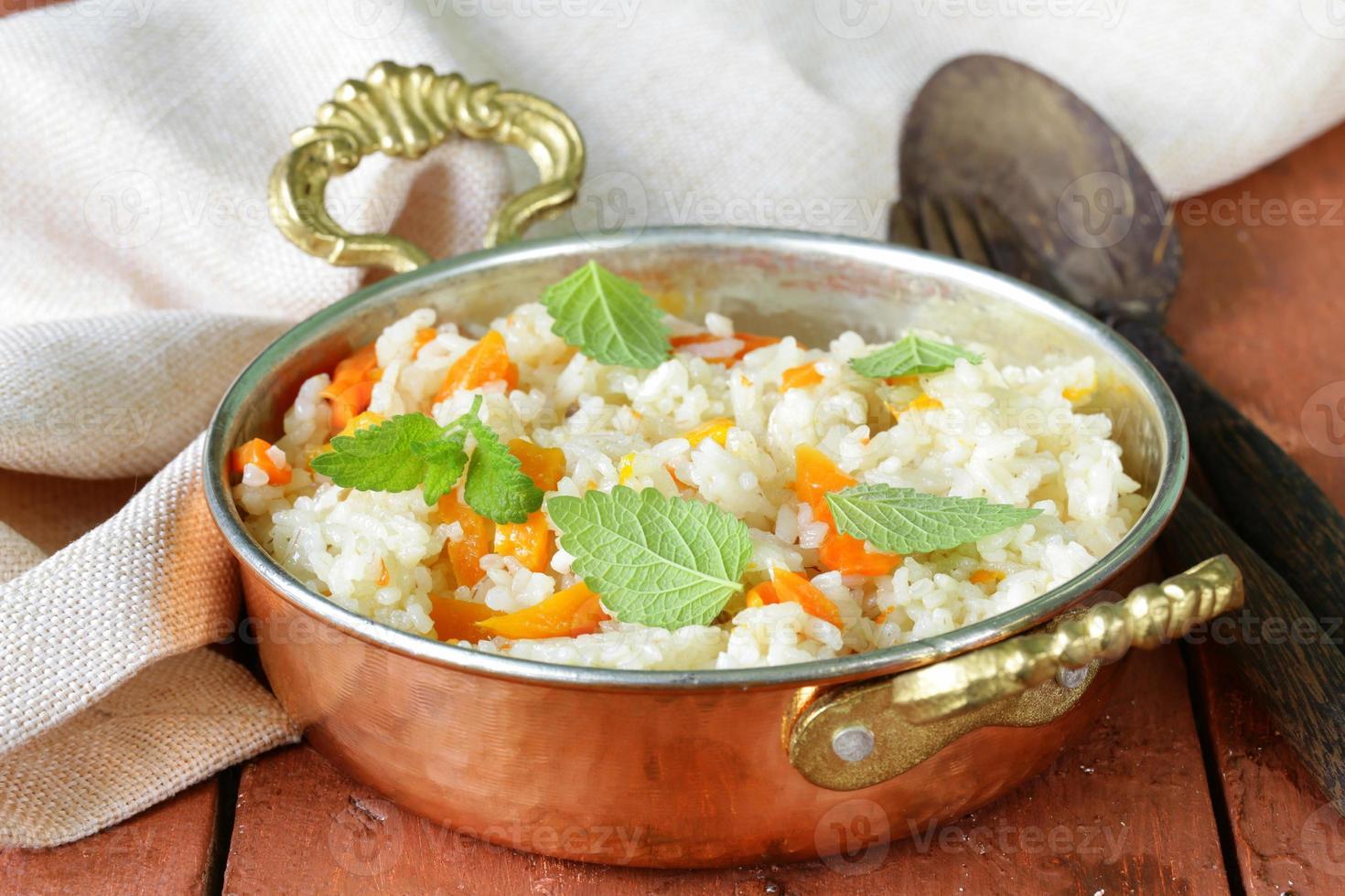 arroz com legumes cozidos em estilo indiano em uma panela de cobre foto