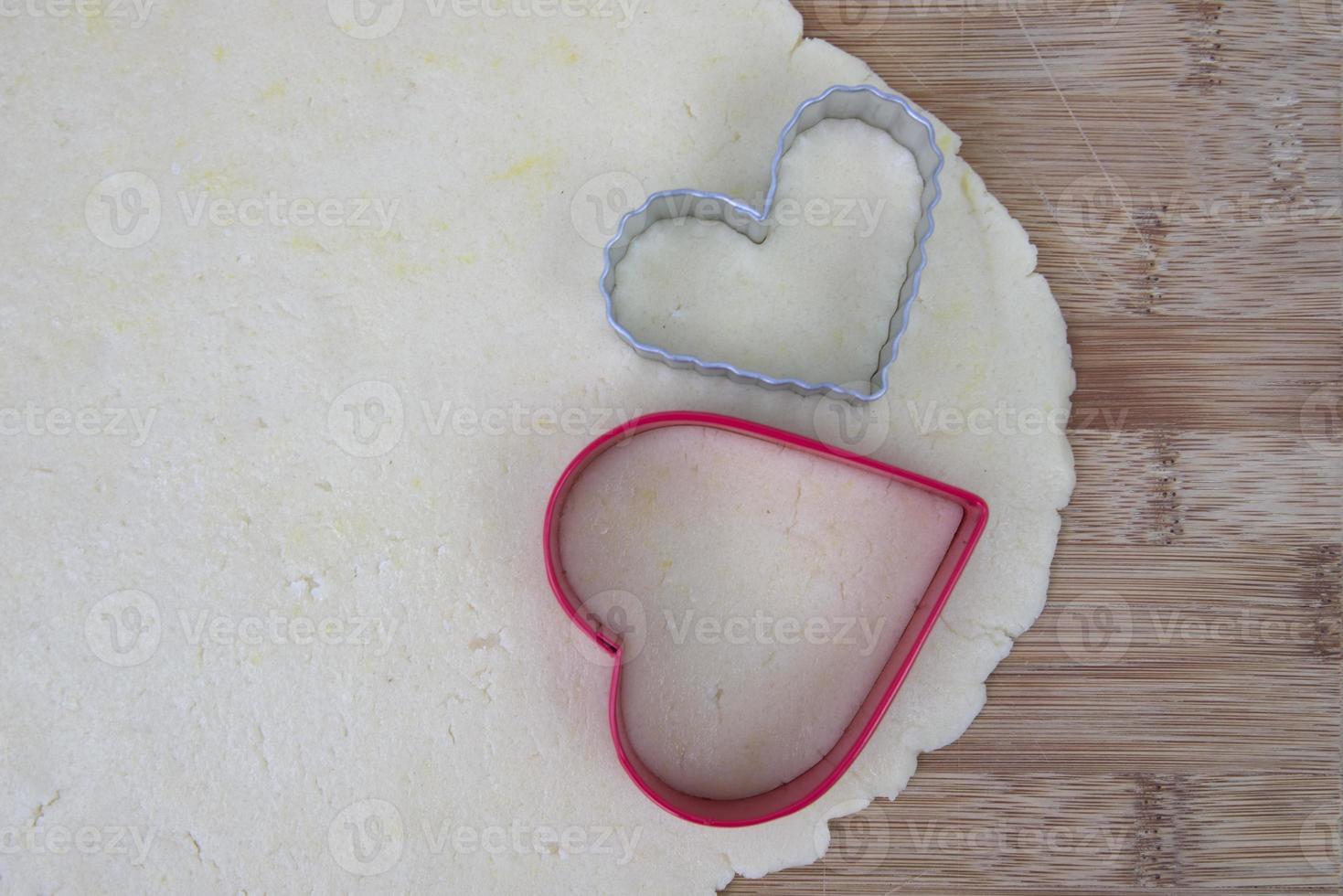 massa de biscoito de açúcar com cortadores em forma de coração foto