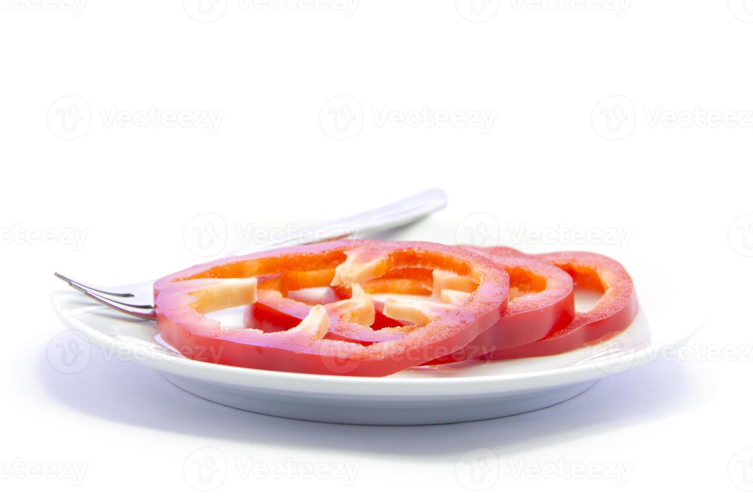 pimentão vermelho sino fatiado ingrediente na chapa branca foto