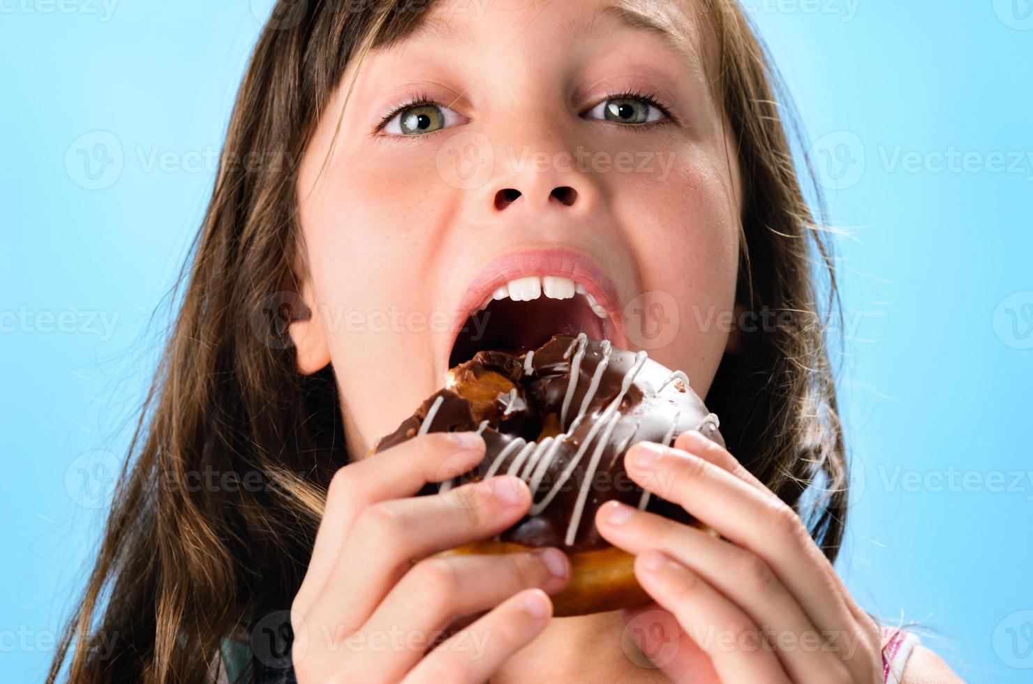 garoto bonito comendo rosquinha foto