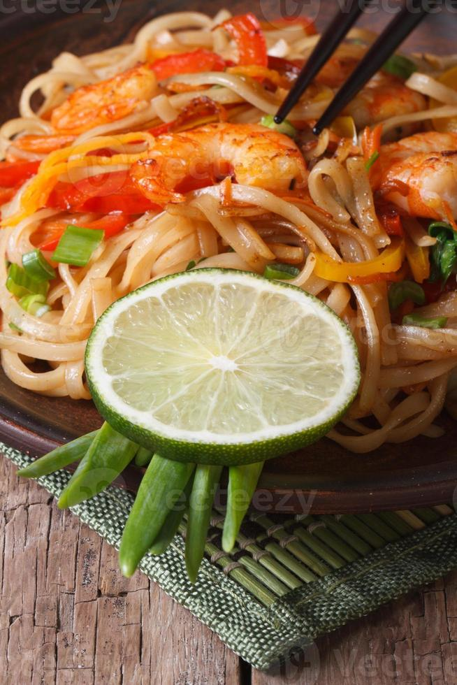 macarrão de arroz delicioso com camarão e legumes verticais foto