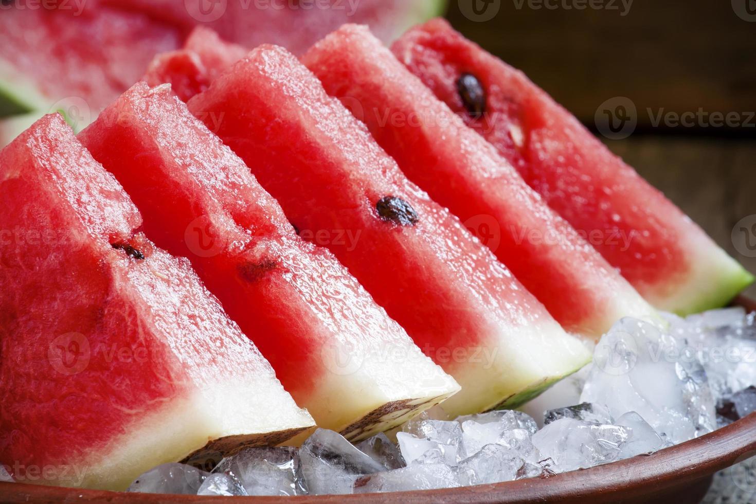 fatias de melancia com gelo em um prato de barro foto