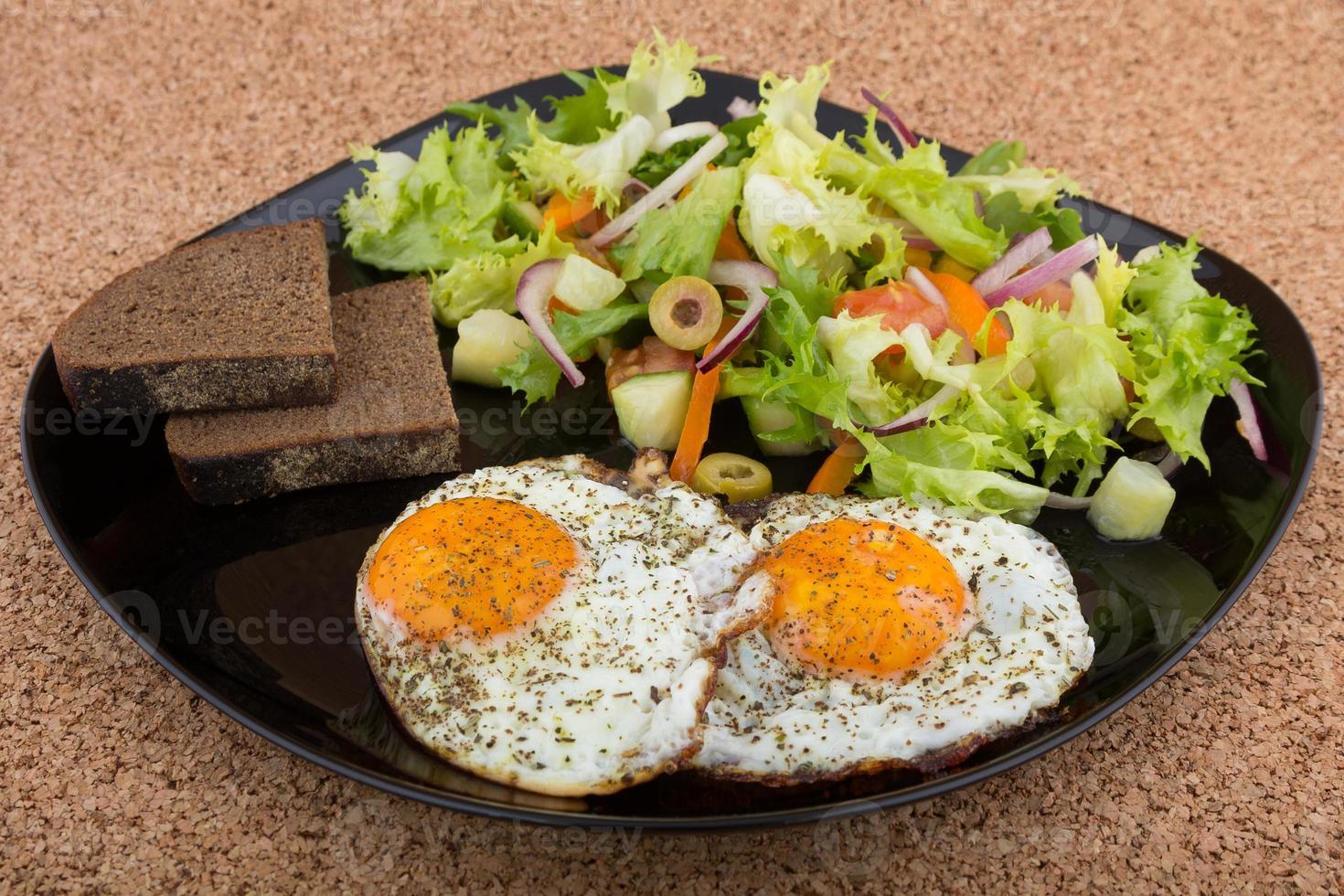 ovos fritos com salada e pão frescos foto