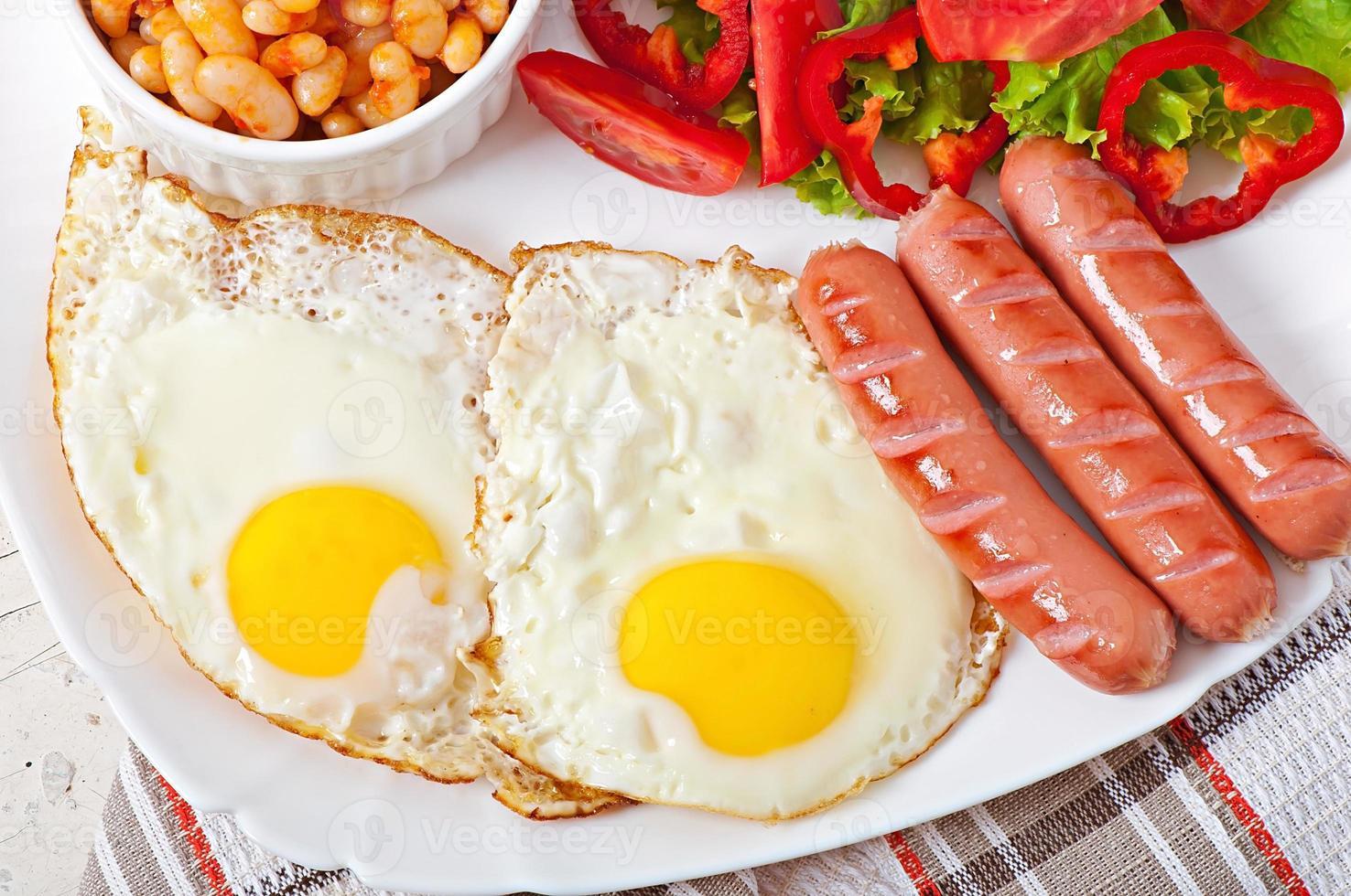 café da manhã inglês - salsichas, ovos, feijão e salada foto