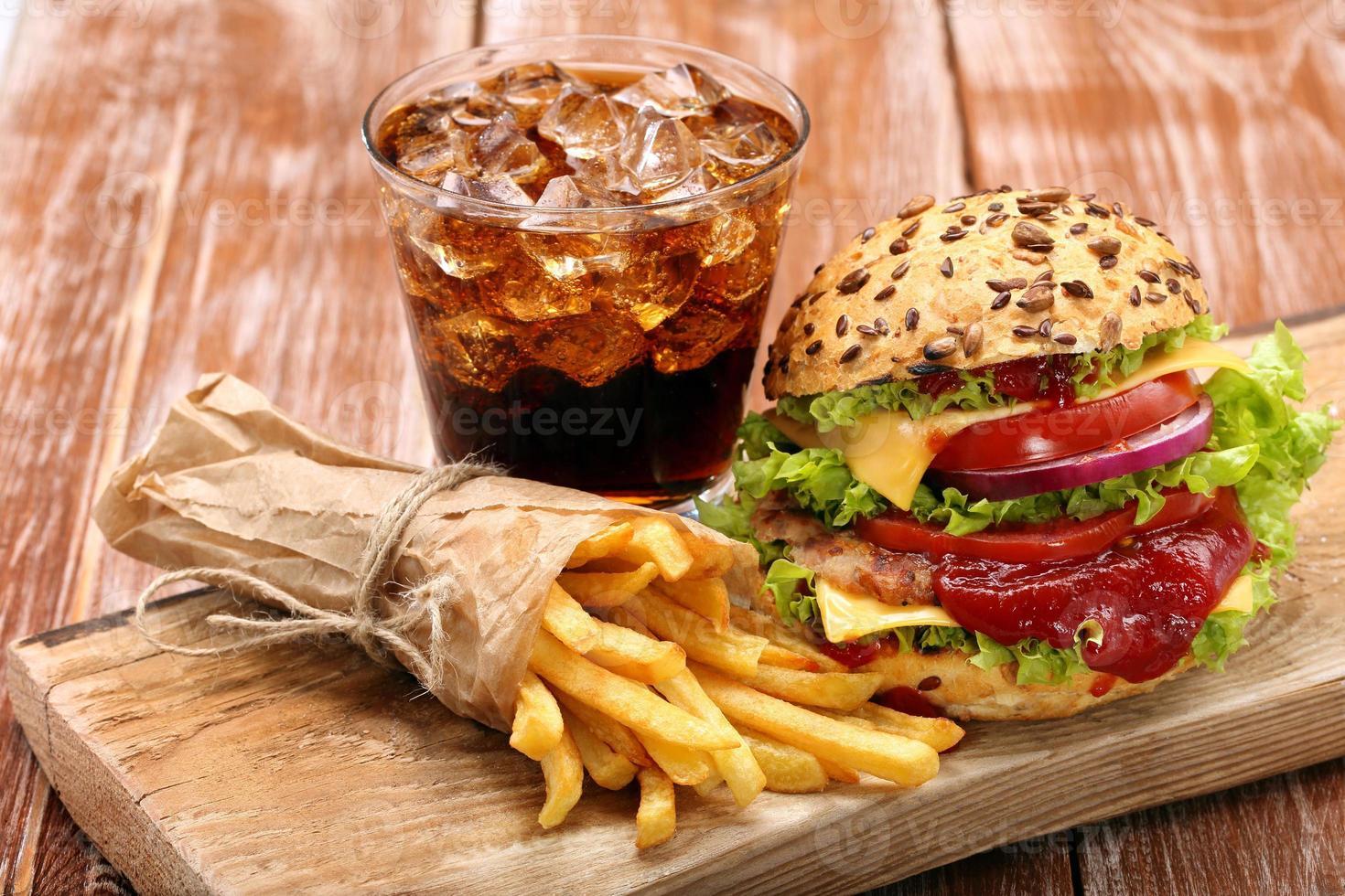 hambúrguer grelhado com batatas fritas e cola no fundo da parede de tijolo foto